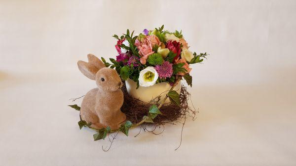 Osternest - Straußenei mit frischen Frühlingsblumen und Hasen