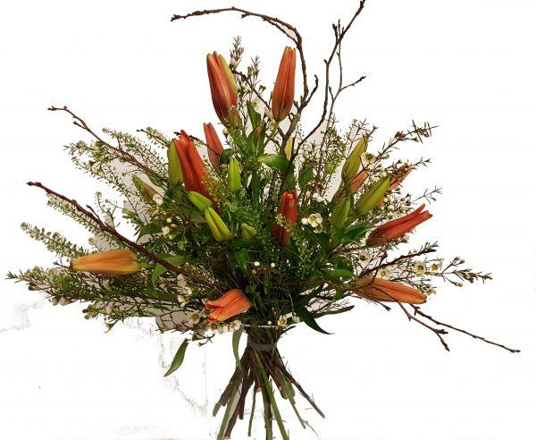 wildromantischer Blumenstrauß mit Zweigen und orangenen Lilien im Landhausstil