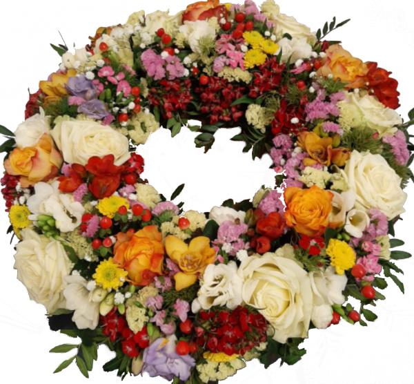 Farbenfroher Trauerkranz mit vielen verschiedenen frischen Trauerblumen